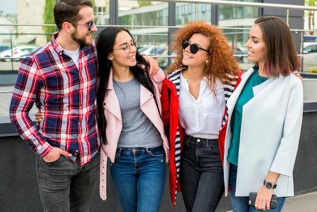Grupo de amigos alegres em pé perto do edifício de vidro Foto gratuita