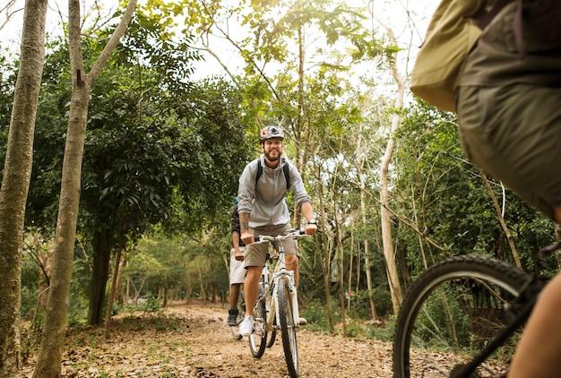 Grupo de amigos andam de bicicleta de montanha na floresta juntos Foto gratuita
