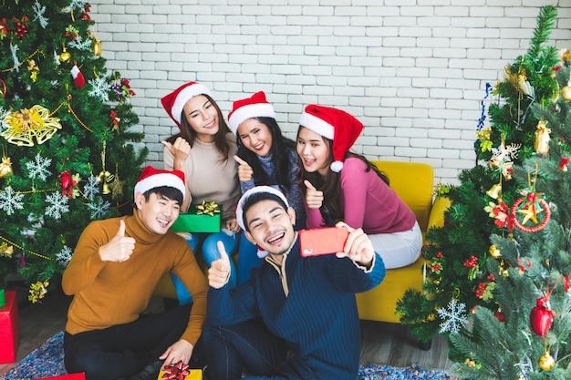 Grupo de amigos asiáticos tomando selfie com o amigo juntos pelo smartphone em casa durante a festa de véspera de natal ou ano novo comemorar festa. feliz inverno xmas e feliz ano novo conceito de festa Foto Premium