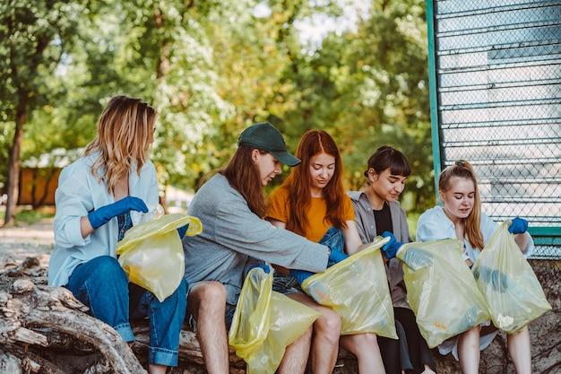 Grupo de amigos ativistas coletando resíduos plásticos no parque Foto gratuita