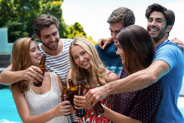 Grupo de amigos brindando a garrafas de cerveja perto da piscina Foto Premium