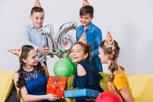 Grupo, de, amigos, celebrando, aniversário, dar, presentes, e, segurando, sliver, número, 16, folha, balloon Foto gratuita