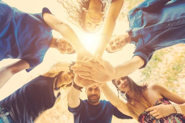 Grupo de amigos com as mãos na pilha e olhando para baixo Foto Premium