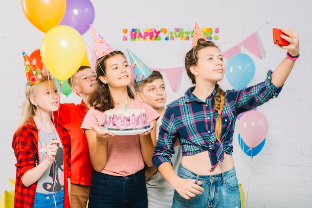Grupo de amigos com bolo de aniversário tomando selfie no celular Foto gratuita