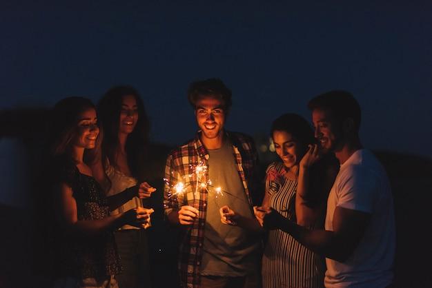 Grupo de amigos com sparklers Foto gratuita