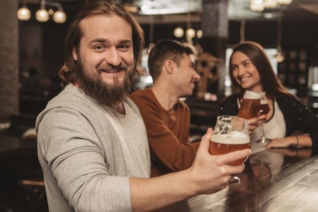 Grupo de amigos comemorando no pub, bebendo cerveja juntos Foto Premium