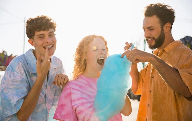 Grupo de amigos comendo algodão doce Foto gratuita