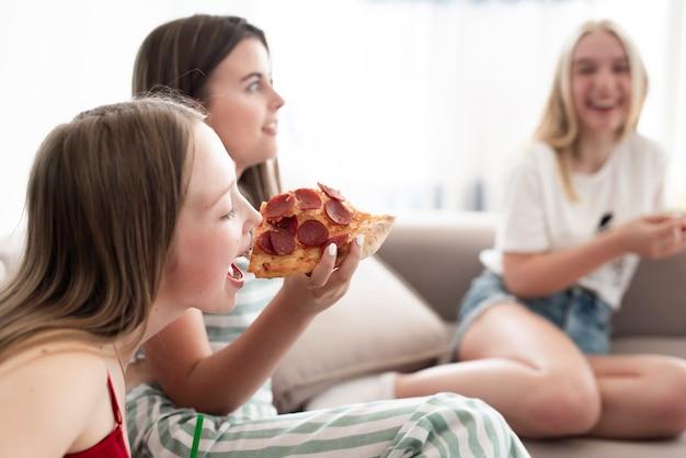Grupo de amigos comendo pizza Foto gratuita
