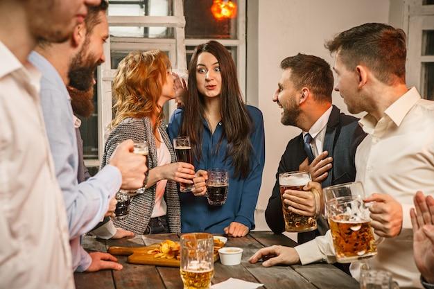 Grupo de amigos curtindo drinks à noite com cerveja Foto gratuita