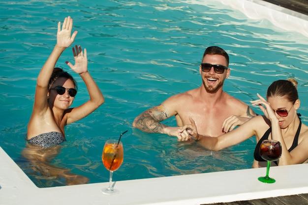 Grupo de amigos dançando na água na festa na piscina. Foto Premium