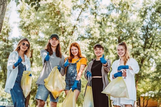 Grupo de amigos de ativistas, coleta de lixo plástico. caras aparecem polegar para cima. Foto gratuita
