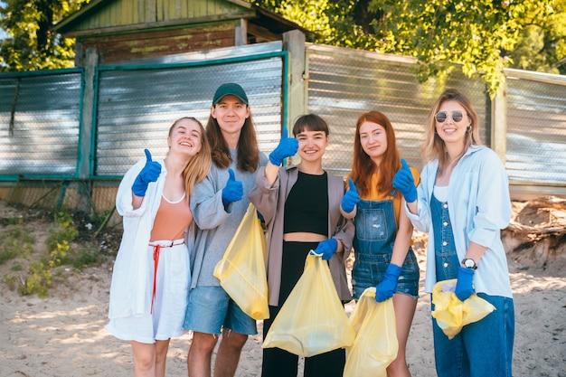Grupo de amigos de ativistas que coletam resíduos plásticos na praia. caras aparecem polegar para cima. Foto gratuita