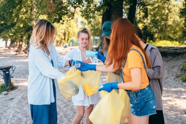 Grupo de amigos de ativistas que coletam resíduos plásticos na praia. conservação ambiental. Foto gratuita