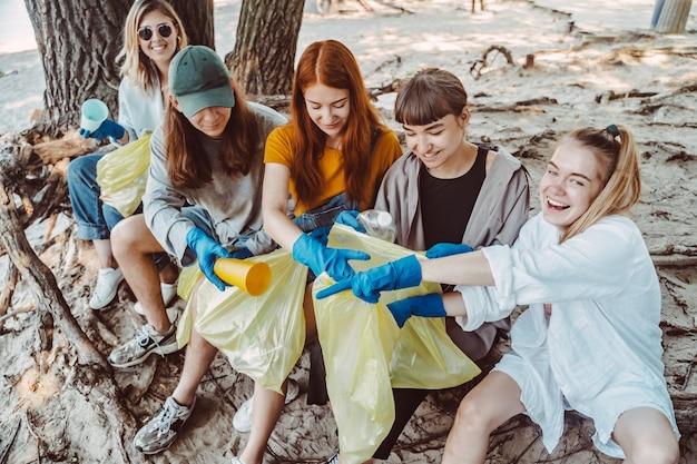 Grupo de amigos de ativistas que coletam resíduos plásticos no parque. conservação ambiental. Foto gratuita