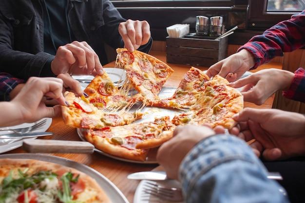 Grupo de amigos de estudantes comem pizza italiana, mãos levam fatias de pizza em um restaurante Foto Premium