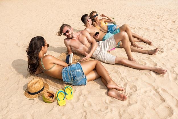 Grupo de amigos deitado na praia tomando banho de sol Foto Premium