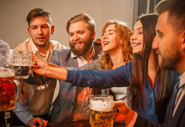 Grupo de amigos, desfrutando de bebidas à noite com cerveja na mesa de madeira Foto gratuita