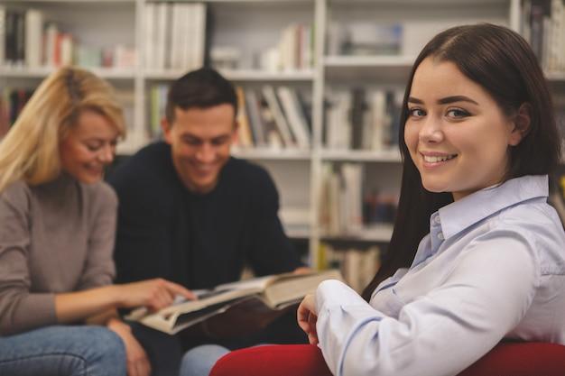 Grupo de amigos, desfrutando de estudar juntos na biblioteca Foto Premium