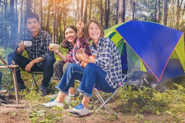 Grupo de amigos desfrutar com bebida quente e tocando ukulele ao lado da tenda. Foto Premium