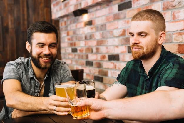Grupo de amigos do sexo masculino brindando copos alcoólicos em bar Foto gratuita