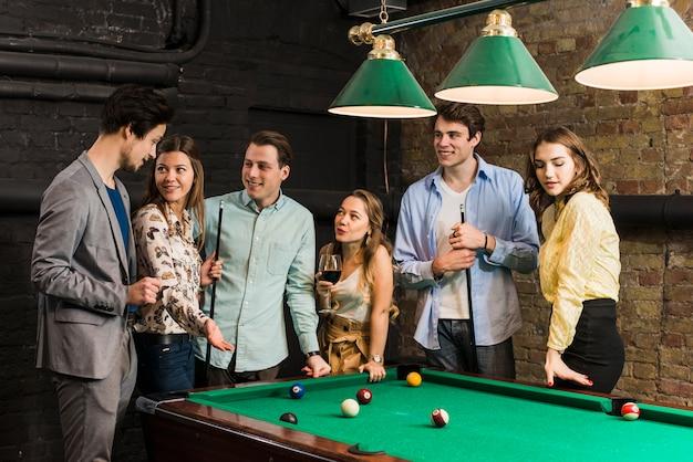 Grupo de amigos do sexo masculino e feminino em pé na mesa de bilhar Foto gratuita
