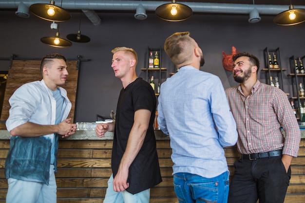 Grupo de amigos do sexo masculino em pé no bar balcão apreciando Foto gratuita