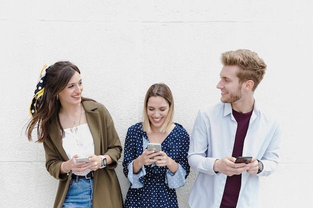 Grupo de amigos em pé perto da parede usando telefone celular Foto gratuita