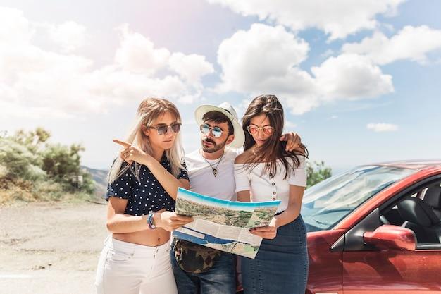 Grupo de amigos em pé perto do carro olhando mapa Foto gratuita