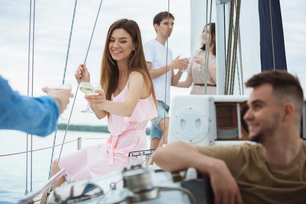 Grupo de amigos felizes bebendo cocktails de vodka em um barco Foto gratuita