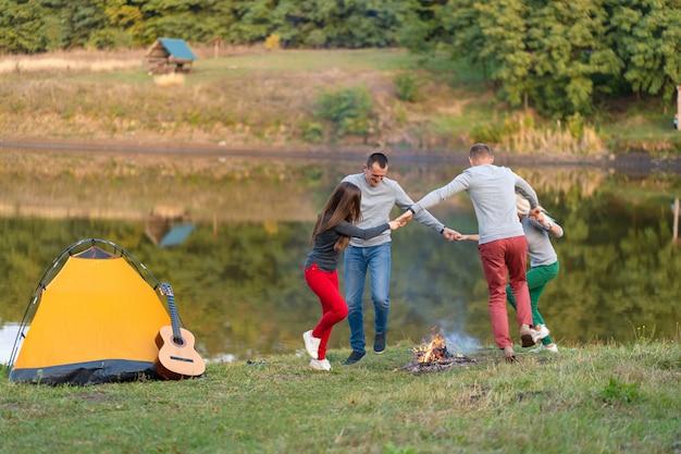 Grupo de amigos felizes com guitarra, se divertindo ao ar livre, dançando e pulando perto do lago no parque, o lindo céu. diversão em camping Foto Premium
