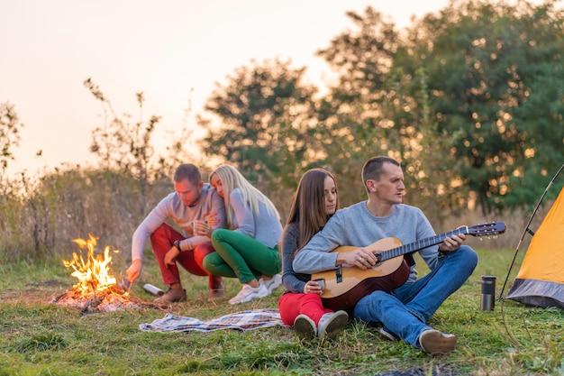 Grupo de amigos felizes com guitarra, se divertindo ao ar livre, perto da barraca da fogueira e do turista. diversão de acampamento família feliz Foto Premium