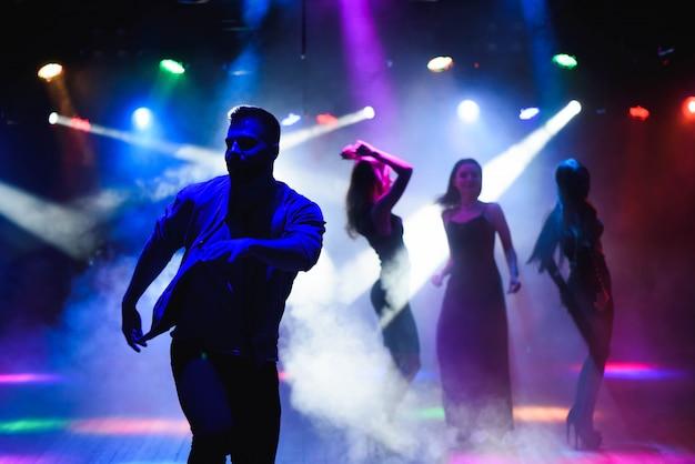 Grupo de amigos felizes dançando na boate Foto Premium