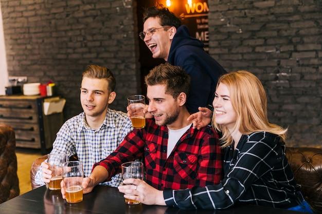 Grupo de amigos felizes sentados juntos apreciando a cerveja no restaurante Foto gratuita