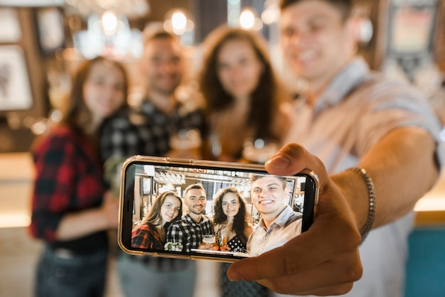 Grupo de amigos felizes tomando selfie no celular Foto gratuita