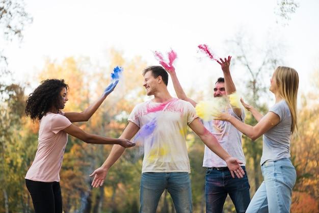 Grupo de amigos jogando cor em pó no ar Foto gratuita