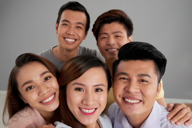 Grupo de amigos masculinos e femininos asiáticos posando juntos Foto gratuita