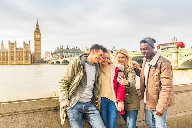 Grupo de amigos multirraciais feliz usando smartphone em londres Foto Premium