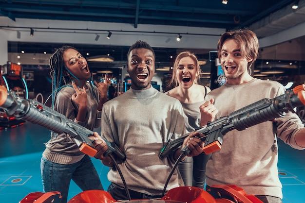 Grupo de amigos no arcade. cara com armas. Foto Premium
