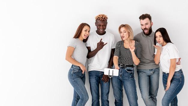 Grupo de amigos no espaço da cópia tirando selfies Foto gratuita