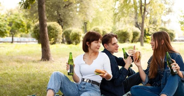 Grupo de amigos no parque com hambúrgueres e cerveja Foto gratuita