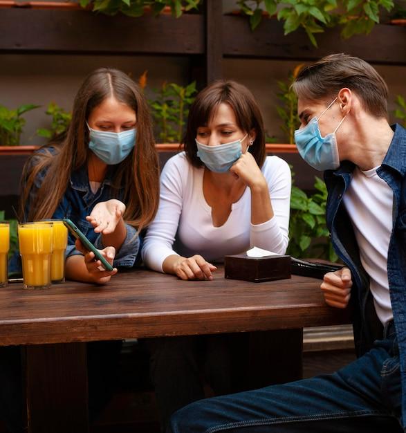 Grupo de amigos olhando para o smartphone enquanto toma um suco Foto gratuita