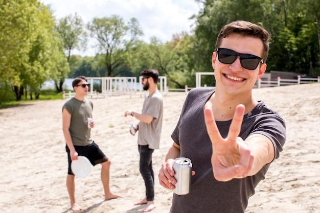 Grupo de amigos relaxantes com bebidas lá fora Foto gratuita