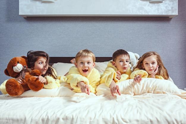 Grupo de amigos se divertindo na cama. crianças rindo felizes, meninos e meninas brincando na cama branca no quarto. Foto gratuita
