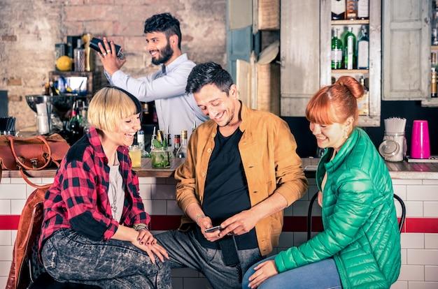 Grupo de amigos se divertindo usando o smartphone no restaurante hipster bar Foto Premium