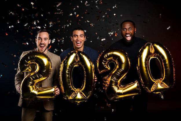 Grupo de amigos segurando balões na festa de ano novo Foto gratuita
