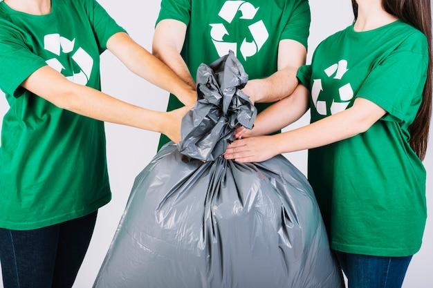 Grupo de amigos segurando o saco de lixo Foto gratuita