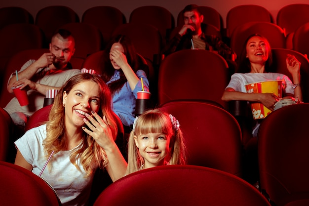 Grupo de amigos sentado na sala de cinema com pipoca e bebidas Foto Premium
