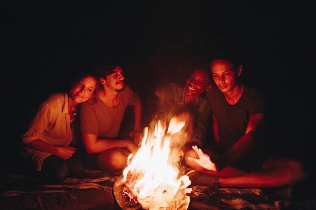 Grupo de amigos sentados ao redor de uma fogueira em um acampamento Foto gratuita