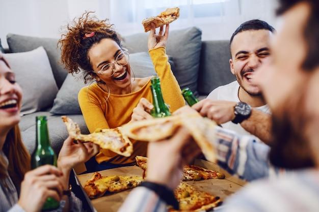 Grupo de amigos sentados no chão da sala, bebendo cerveja e comendo pizza. Foto Premium