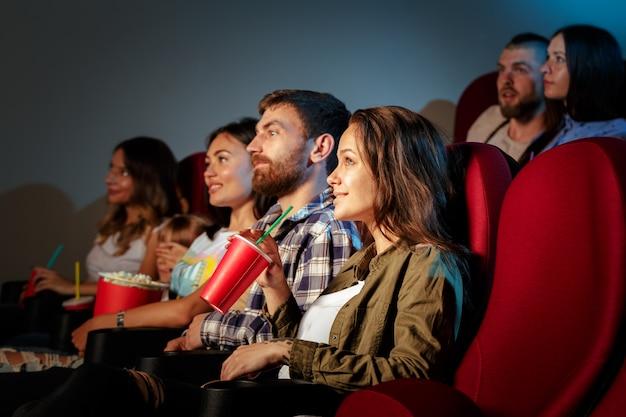 Grupo de amigos sentados no cinema com pipoca e bebidas Foto Premium